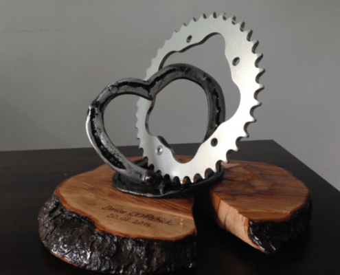 wedding present - Connection of a heart made of horseshoes and a sprocket fixed on an engraved wooden plate.